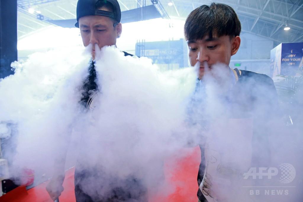 美女も豪快に鼻から「ふーっ」、中国・電子たばこ展示会
