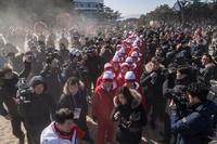 北朝鮮「美女応援団」のビーチ訪問にメディア殺到 屋外で演奏披露も