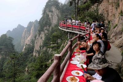命懸けの食事会?断崖絶壁で観光イベント 中国・老君山