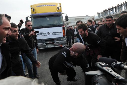 片耳で8トントラックを動かすギネス記録、グルジア男性が挑戦