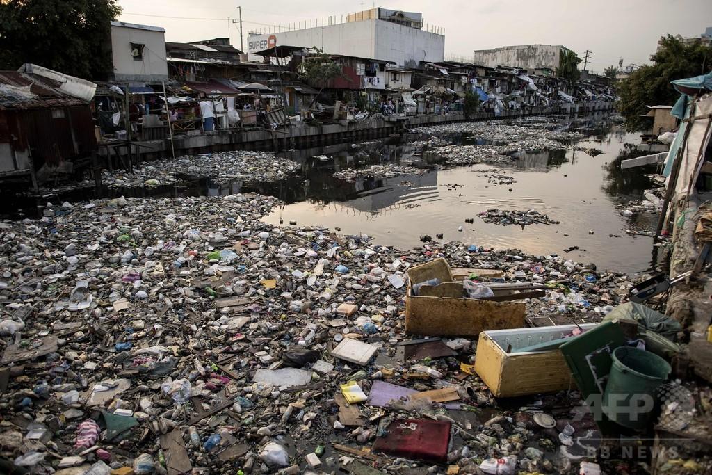 まるで「舗道」、ぎっしり川を覆うごみ マニラ