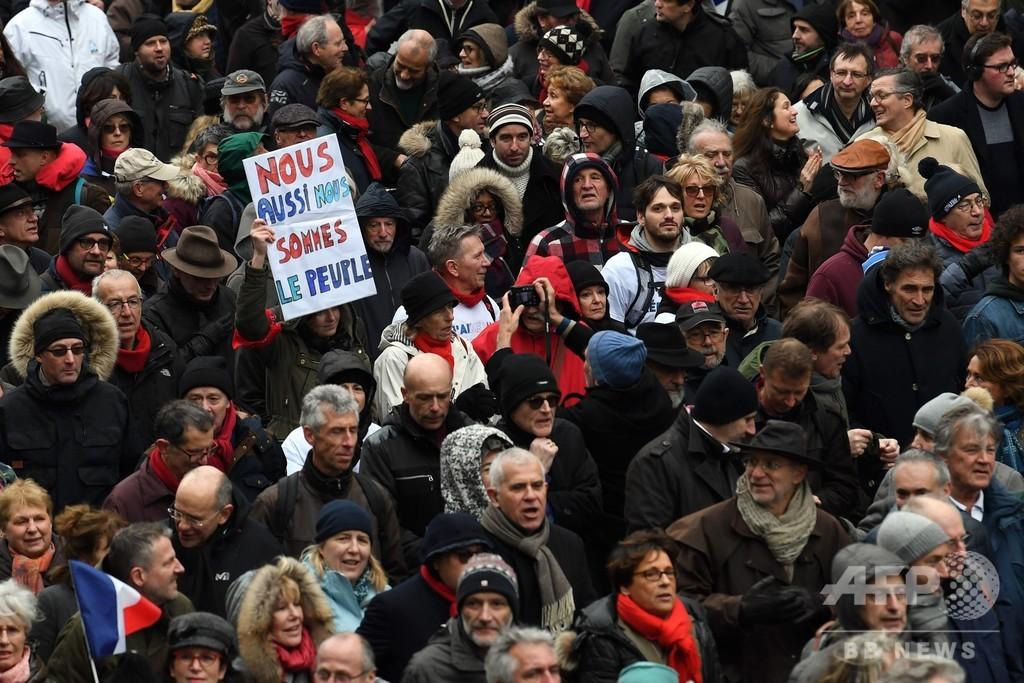 パリで「赤いスカーフ」隊がデモ 「黄色いベスト」の暴力に1万人超が抗議