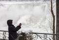 凍り付いたナイアガラの滝に集まる観光客ら