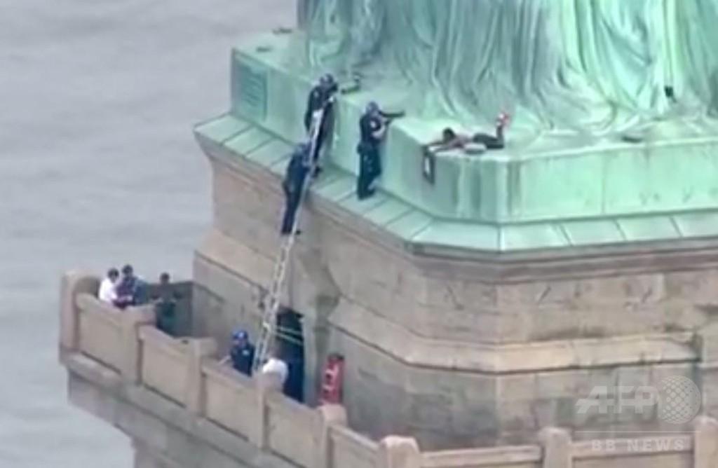 「自由の女神」に女よじ登る トランプ政権の移民政策に抗議