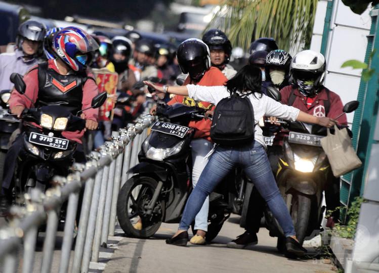 歩道にオートバイ、体張って「ストップ」!インドネシア女性に称賛