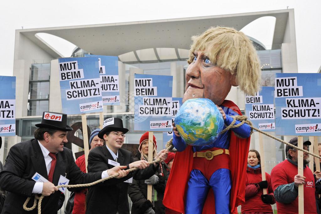 メルケル首相はスーパーマン? ドイツで環境政策に対する抗議デモ