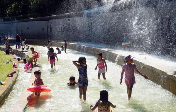 東京で35度の猛暑日、噴水で遊ぶ子どもたち