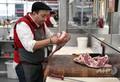 豪メルボルン郊外の精肉店で、国産のラム肉を切り分ける店員(2020年5月12日撮影)。(c)William WEST / AFP