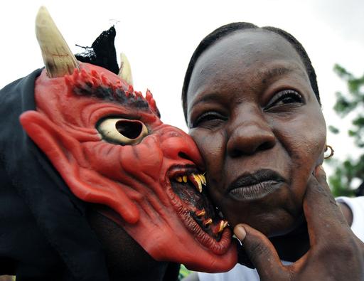 コートジボワールのカーニバル、悪魔も浮かれてキス