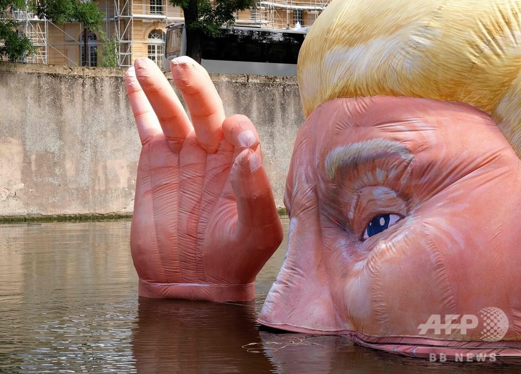 頭の半分が水没したトランプ人形、仏アートフェスに登場