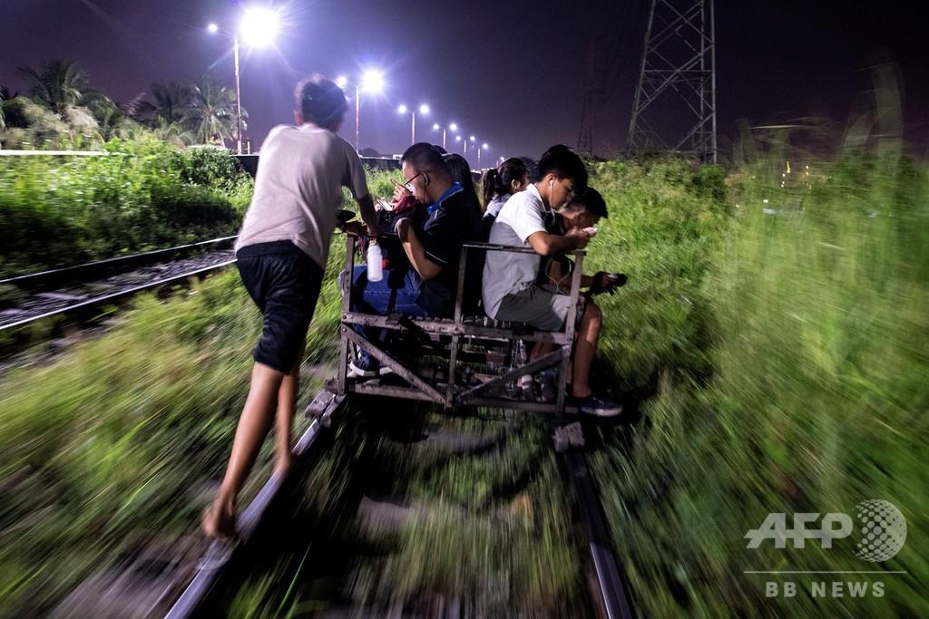 庶民の足は危険と隣り合わせ、線路を走る「乗り合いトロッコ」 マニラ