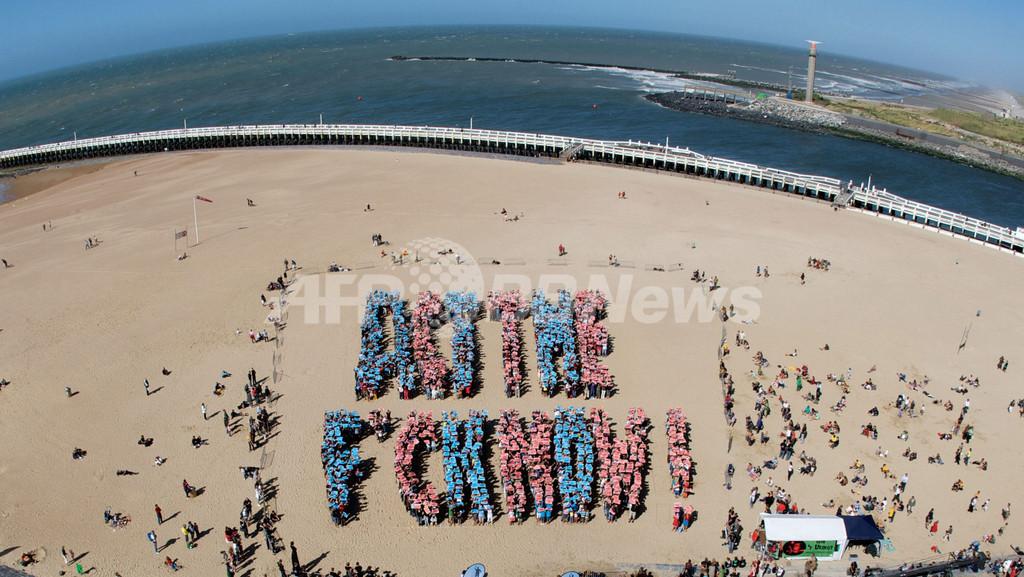 砂浜に「今こそ行動を!」の人文字、温暖化対策をアピール