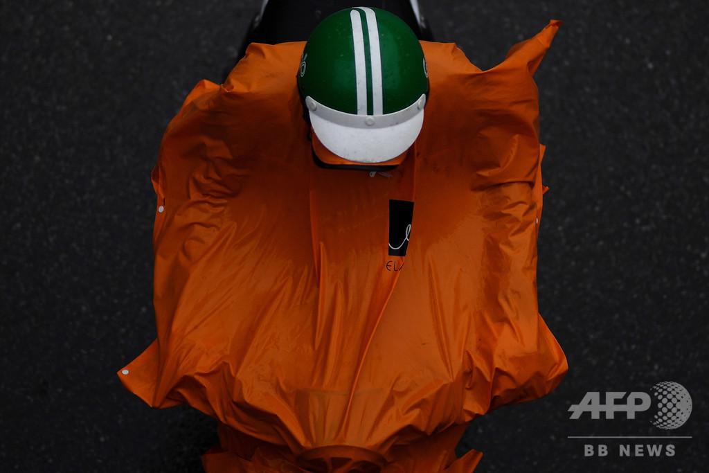 カラフルな雨がっぱのバイカーたち、雨模様のハノイがにぎやかに ベトナム