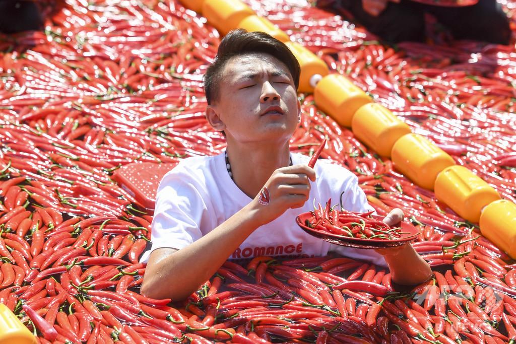 収穫を「涙」で祝う、トウガラシの大食いコンテスト 会場はプール
