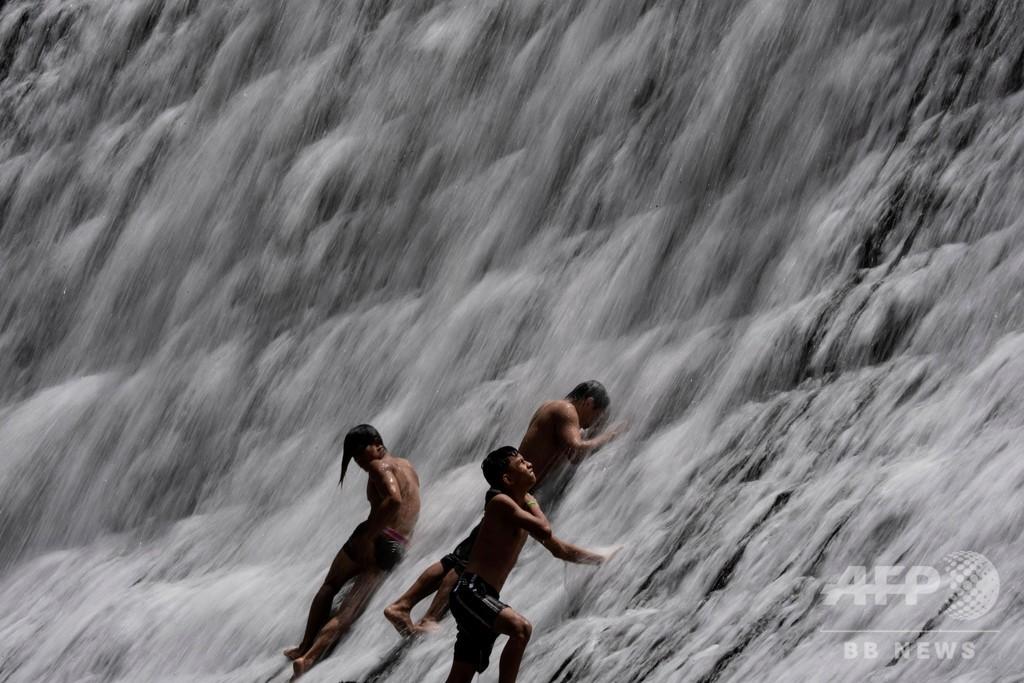 水浴びは豪快に、役割終えたダムで涼む人々 フィリピン
