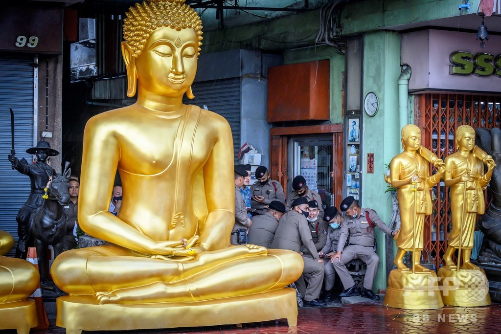 【今日の1枚】仏の慈悲の雨宿り、タイの警察官