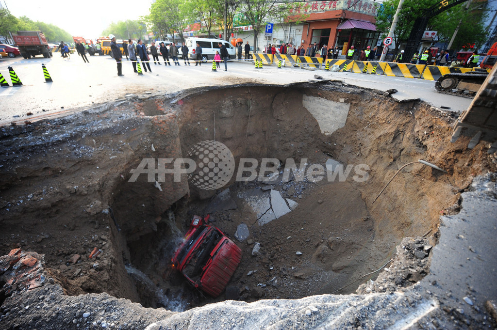 道路陥没で巨大な穴、原因は地下鉄工事?北京