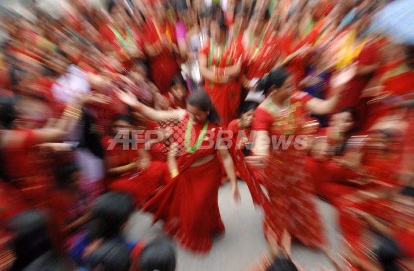 深紅のサリーで女性ら舞い踊る、ヒンズー教祭「ティージ」