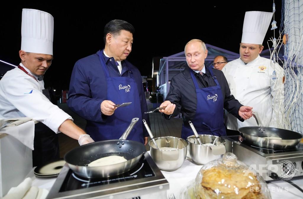 エプロン姿の中ロ首脳、パンケーキ焼く 経済フォーラム関連行事
